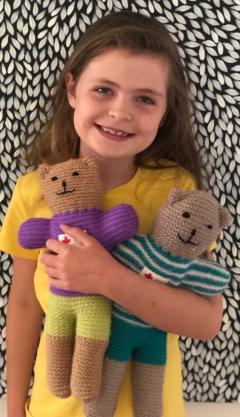 little girl cuddling trauma teddies